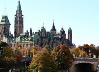 The Canadian flag flies over the Parliament hill in Ottawa, Canada on October 22, 2014. A gun man opened fire at the National War Memorial and killed an soldier and then went into the Parliament Hill in Ottawa and fired several shots in the building. Gunfire echoed through the Gothic halls of the Canadian parliament Wednesday as police shot dead a gunman who had killed a soldier guarding a nearby war memorial before storming the building. Police said an investigation was continuing, but did not confirm earlier reports that more gunmen were involved. Heavily armed officers backed by armored vehicles sealed off the building. There was no immediate word on the gunman's motivation, but the attack came a day after an alleged Islamist drove over and killed another soldier in what authorities branded a terrorist attack. AFP PHOTO / Lars Hagberg (Photo credit should read Lars Hagberg/AFP/Getty Images)